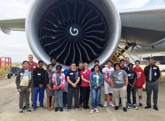 Aviation academy students in front of jet engine