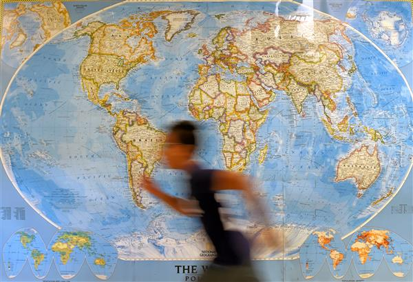Student running in front of a world map