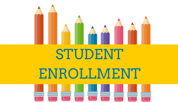 student enrollment sign on yellow background ith colorful pencils standing behind it